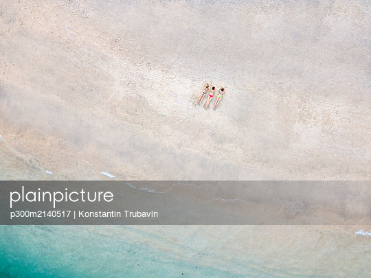 Aerial view of young women lying at the beach, Gili Air island, Bali, Indonesia - p300m2140517 by Konstantin Trubavin