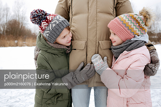 Two smiling siblings together with father in winter - p300m2160076 von Ekaterina Yakunina