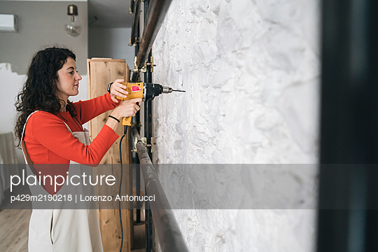 Mid adult woman drilling wall in her new shop - p429m2190218 by Lorenzo Antonucci