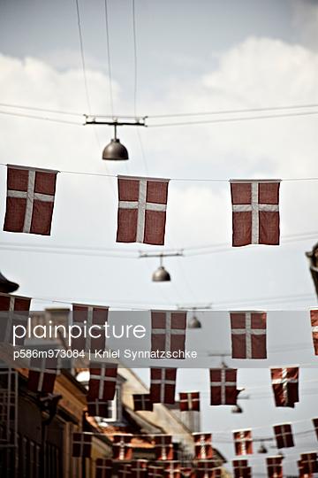 Nationalflaggen Dänemarks über einer Straße - p586m973084 von Kniel Synnatzschke