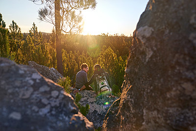 Affectionate young hiker couple relaxing on rock in sunny sunset woods - p1023m2212967 by Trevor Adeline