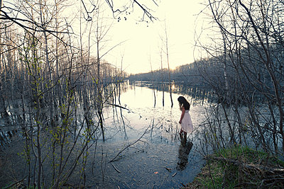 A woman in a white dress wading in shallow water at dusk. - p1100m1027677f by Mint Images