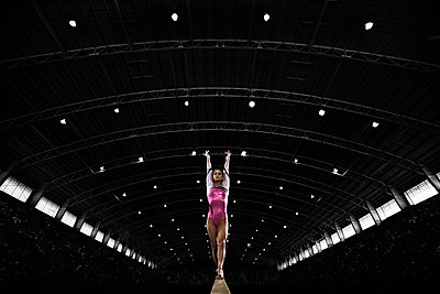 A young woman gymnast performing on the beam, balancing on a narrow piece of apparatus. - p1100m1095651 by Mint Images