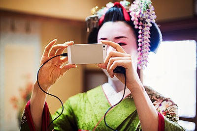 A woman dressed in the traditional geisha style, wearing a kimono and obi, with an elaborate hairstyle and floral hair clips, with white face makeup with bright red lips and dark eyes. Taking a selfie.  - p1100m1185708 by Mint Images