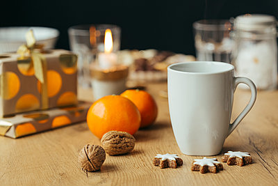 Cup of tea, tangerines, walnuts,  cinnamon stars and Christmas presents in the background - p300m1505692 by Julia Haack