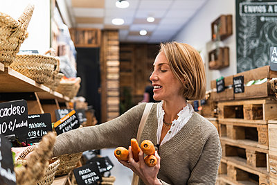 Blond woman collecting carrots in supermarket - p300m2286901 by NOVELLIMAGE