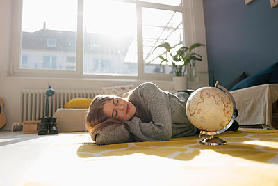 Young woman alongside globe in her apartment - p586m2021377 by Kniel Synnatzschke