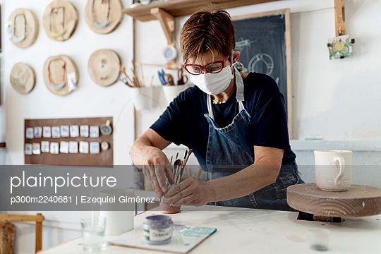 Female artist working in ceramic workshop during COVID-19 - p300m2240681 by Ezequiel Giménez