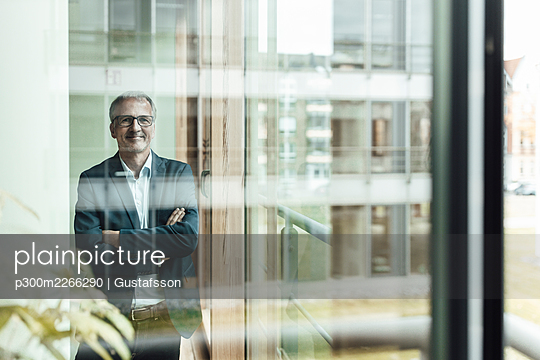 Smiling businessman with arms crossed seen through glass in office corridor - p300m2266290 by Gustafsson