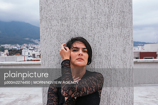 Beautiful woman with hand in hair standing in front of architectural column - p300m2274450 by MORNINGVIEW AGENCY