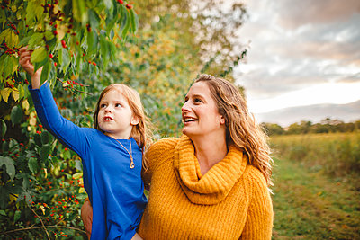 A happy woman holds her daughter up to explore red berries on a tree - p1166m2151944 by Cavan Images