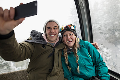 Affectionate, enthusiastic skier couple riding gondola, taking selfie with smart phone - p1192m1546592 by Hero Images
