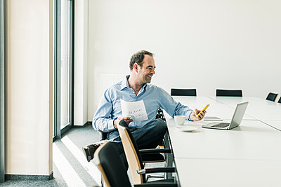 Confident businessman using cell phone in conference room - p300m1416553 by Uwe Umstätter