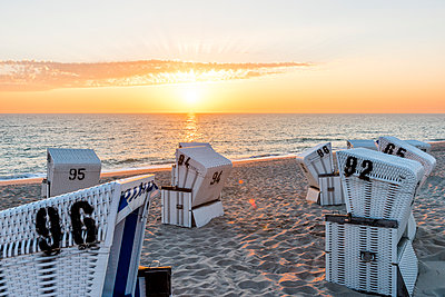 Germany, Schleswig-Holstein, Sylt, beach and empty hooded beach chairs at sunset - p300m1587451 von Ega Birk