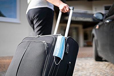 Tourist pulling wheeled luggage while walking towards hotel during coronavirus - p300m2253218 by Annika List