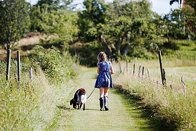 Girl walking dog - p312m1229279 by Anna Kern