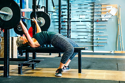 Caucasian woman lifting barbell on bench in gymnasium - p555m1303187 by Inti St Clair