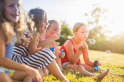 Girls blowing bubbles in grass field - p555m1411524 by John Fedele