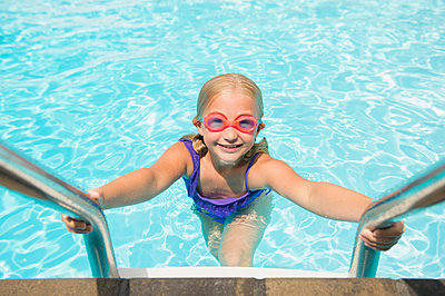 Caucasian girl climbing out of swimming pool - p555m1421667 by JGI/Jamie Grill