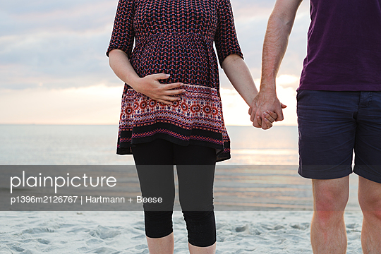 Pregnant woman and partner on the beach - p1396m2126767 by Hartmann + Beese