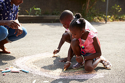 Brother and sister coloring rainbow with chalk on sunny sidewalk - p1023m2238492 by Himalayan Pics