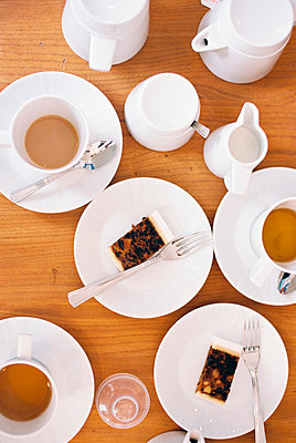 Overhead view of a table set with cups of tea, milk jugs and two slices of fruit cake on plates.  - p1100m962190f by Britt Chudleigh