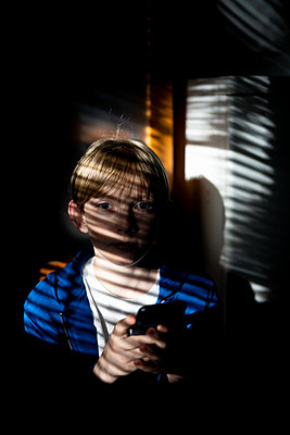 Tween holding cell phone looking at camera indoors in mottled light - p1166m2212337 by Cavan Images