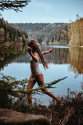 Frau posiert vor ruhigem Bergsee - p1455m2203726 von Ingmar Wein