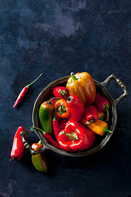 Bowl of various organic bell peppers and chili peppers on dark ground - p300m2041734 by Dieter Heinemann