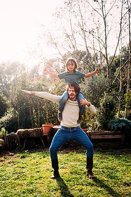 Father playing with his son, carrying him piggyback in a garden - p300m2070468 von Gemma Ferrando