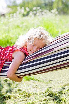 Girl sleeping in hammock in field - p31227435f by Ulf Huett Nilsson