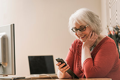 Woman smiling, using mobile phone at work desk - p429m1206788 by Colin Hawkins
