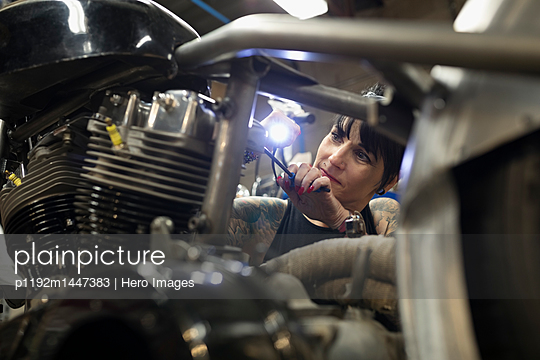 Female motorcycle mechanic fixing engine in auto repair shop