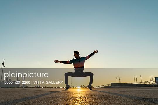 Acrobat doing movement training in city at sunrise - p300m2012260 von VITTA GALLERY