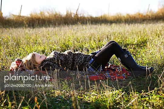 Girl lying on grass - p312m2092120 by Anna Kern