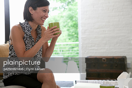 Mature office worker holding mug and smiling