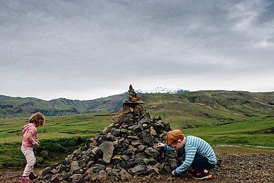 Siblings playing by heap of rocks on field against cloudy sky - p1166m2001349 by Cavan Images