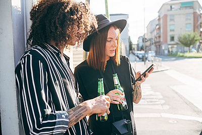 Couple holding beer bottles using smart phone while standing on street in city - p300m2206876 by Eugenio Marongiu
