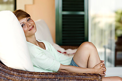 Smiling brunette woman relaxing - p300m948695f by Gabi Dilly