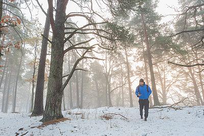A man walking through a snowy forest - p352m1523750 by Calle Artmark