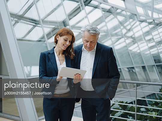 Smiling businessman and businesswoman using tablet in modern office building - p300m2155457 by Joseffson