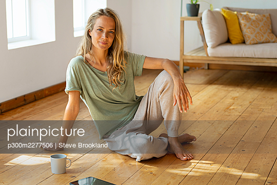 Relaxed woman sitting on floor in living room - p300m2277506 by Steve Brookland