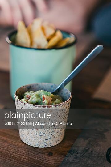 Close up fresh, homemade tortilla chips and guacamole - p301m2123158 by Alexandra C. Ribeiro