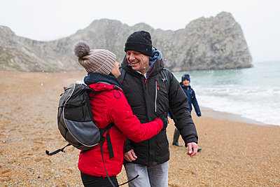 Affectionate, happy couple in warm clothing on snowy winter beach - p1023m2024276 by Sam Edwards