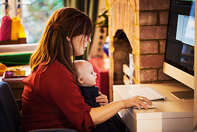 A woman seated with a baby on her lap using her computer, both watching the screen.  - p1100m1425072 by Mint Images