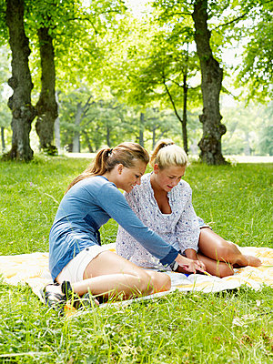Young women sitting on blanket in park - p31224979f by Fredrik Nyman