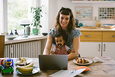 Smiling woman using laptop while sitting with daughter at dining table in house - p426m2046105 by Maskot
