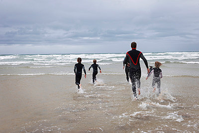 Family running in to the sea in wetsuits - p42911815f by Adie Bush