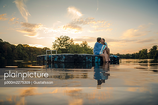 Young couple sitting on bathing platform, kissing, wrapped in towel - p300m2275309 by Gustafsson