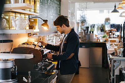 Man in a cafe sorting cups - p300m1588186 von Kniel Synnatzschke